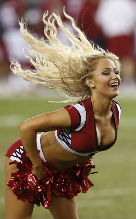 An Arizona Cardinals cheerleader performs during the second half of an NFL preseason football game against the Cincinnati Bengals Sunday, Aug. 24, 2014, in Glendale, Ariz. The Bengals defeated the Car
