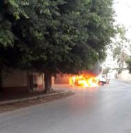 A burning car is seen in front of the Russian embassy, as it came under attack in Tripoli October 2, 2013. REUTERS/Stringer