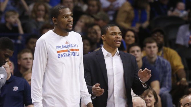 Oklahoma City Thunder forward Kevin Durant, left, and guard Russell Westbrook right, watch from the bench in the fourth quarter of an NBA basketball game against the Sacramento Kings  in Oklahoma City, Sunday, Jan. 19, 2014. Oklahoma City won 108-93