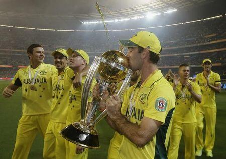 Australia's Maxwell kisses the Cricket World Cup trophy alongside team mates after they defeated New Zealand in the final match at the Melbourne Cricket Ground