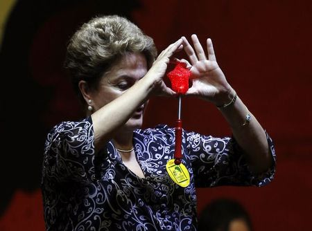 Brazil's President and presidential candidate Dilma Rousseff of the Workers Party (PT) holds a star toy during a meeting with educators in Sao Paulo October 15, 2014. REUTERS/Paulo Whitaker