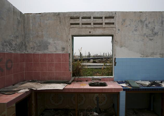 An oil pipeline and construction for the Refinery and Petrochemical Integrated Development project is seen through a window of a house in a village relocated for RAPID's development in Pangerang