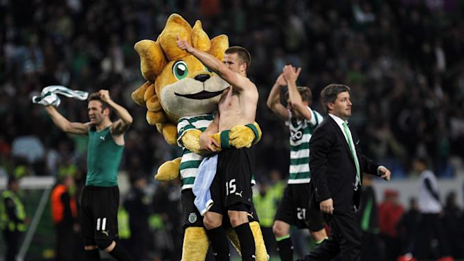 Sporting's president Bruno Carvalho, right, and players Eric Dier, second left, from England, Diego Capel, left, from Spain, and Adrien Silva, second right, from France, celebrate at the end of the Portuguese league soccer match between Sporting and Porto at Sporting's Alvalade stadium, in Lisbon, Sunday, March 16, 2014. Sporting won 1-0