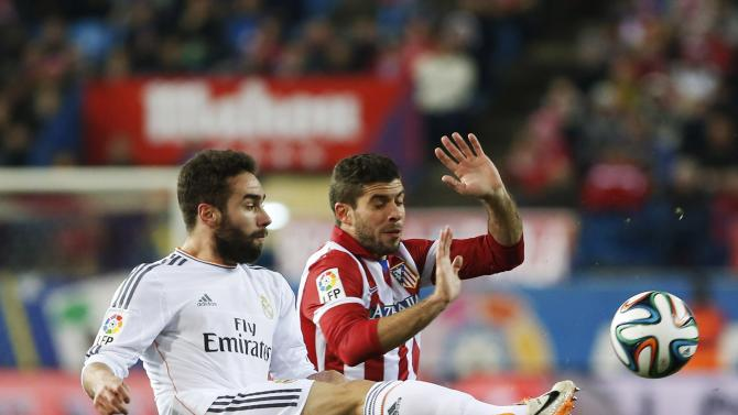 Atletico Madrid's Insua fights for the ball with Real Madrid's Carvajal during their Spanish King's Cup semi-final second leg soccer match at Vicente Calderon stadium in Madrid