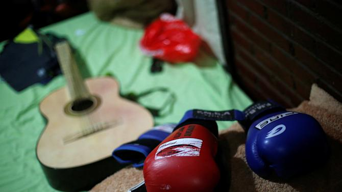 Two boxing gloves are seen next to a guitar after a training session in preparation to Rio 2016 Olympic Games, at a camp 3300 meters above sea level in San Jose Teacalco