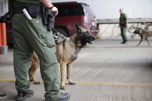 U.S. Customs and Border Patrol agents and K-9 security dogs keep watch at a checkpoint station, Friday, Feb. 22, 2013, in Falfurrias, Texas. Government agencies vary widely in how they are dealing wit