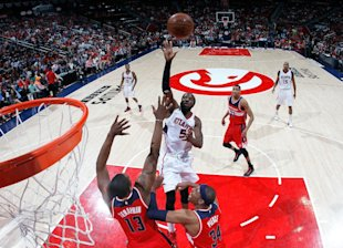 DeMarre Carroll lofts a floater over Kevin Seraphin and Paul Pierce. (Kevin C. Cox/Getty Images)