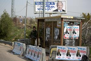 Israeli soldiers stand guard at a bus stop next to…