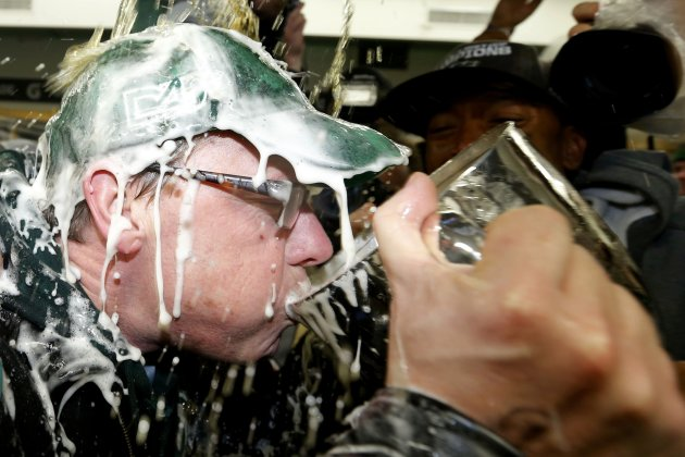 Saskatchewan Premier Brad Wall sips out of the Grey Cup as beer is poured over him (Reuters)
