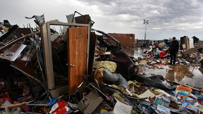 Debris is strewn about amid the wreckage Plaza Towers Elementary, where seven children were killed earlier in the week when a tornado hit Moore, Okla., Thursday, May 23, 2013. The huge tornado roared through the Oklahoma City suburb Monday, flattening entire neighborhoods and destroying the elementary school with a direct blow as children and teachers huddled against winds up to 200 mph. (AP Photo/Brennan Linsley)