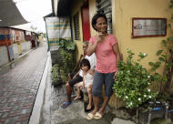 In this photo taken Aug. 3, 2011 in Manila, Philippines, Felisa Morta, right, with her family pause outside their home in a village named after Marie Rose Abad who died during the Sept. 11 2001 terrorist attacks at the World Trade Center in New York City. Unlike many victims of the 2001 attacks who are remembered mostly by their family and friends, Marie Rose Abad's legacy lives on half-way around the world in a once-notorious Manila slum now turned into a tidy village that carries her name. (AP Photo/Pat Roque)