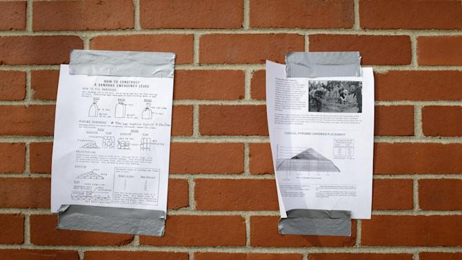 Instructions on how to build a sandbag levee are taped to a building Sunday, April 21, 2013, in Clarksville, Mo. Many have come to the aid of the tiny community, working since Wednesday to build a makeshift sandbag levee that seemed to be holding as the crest, expected to be 11 feet above flood stage, approaches. (AP Photo/Jeff Roberson)
