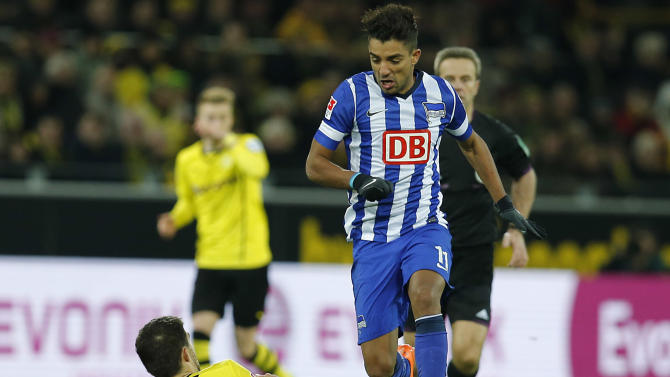 Dortmund's Sokratis of Greece, left, and Berlin's Sami Allagui of Tunesia challenge for the ball during the German first division Bundesliga soccer match between Borussia Dortmund and Hertha BSC Berlin in Dortmund , Germany, Saturday, Dec. 21, 2013