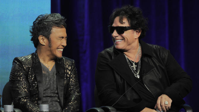 """Arnel Pineda, left, vocalist for the rock band Journey, and guitarist Neal Schon laugh during a panel discussion on the Independent Lens documentary """"Don't Stop Believin': Everyman's Journey,"""" at the PBS Summer 2013 TCA press tour at the Beverly Hilton Hotel on Tuesday, Aug. 6, 2013 in Beverly Hills, Calif. (Photo by Chris Pizzello/Invision/AP)"""