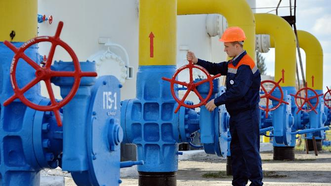 An employee turns a valve of an installation at a gas-pumping station on the pipeline in the small town Boyarka on April 22, 2015