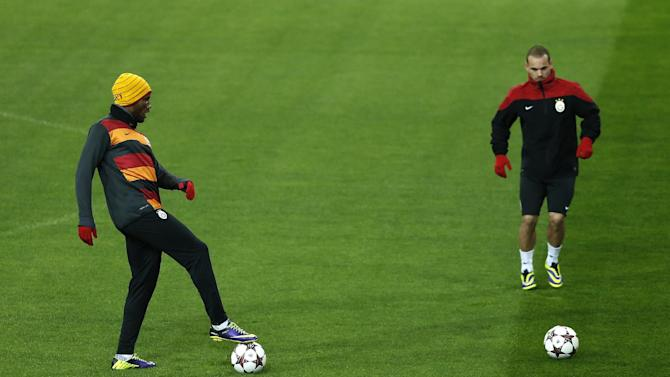 Galatasaray's Didier Drogba from the Ivory Coast, left, and Wesley Sneijder from The Netherlands control the ball during a training session in Madrid, Spain, Tuesday, Nov. 26, 2013.  Galatasaray will play Real Madrid Wednesday in a Group B Champions League soccer match