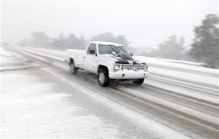 A pickup drives on Highway 44 as heavy snow falls in Rapid City