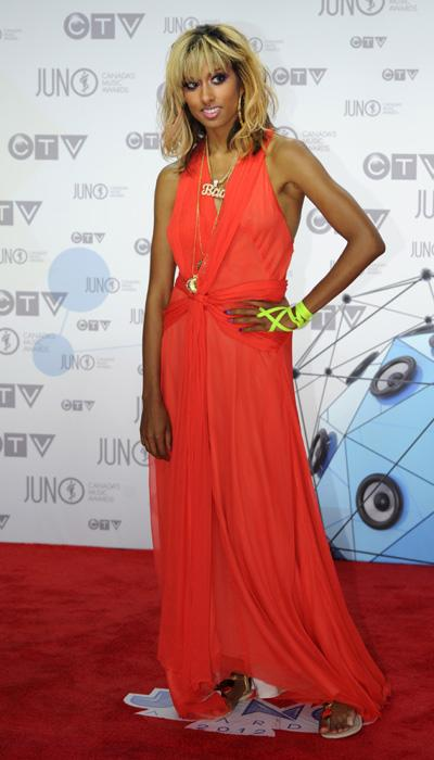 Anjulie is an ethereal goddess in a romantic orange crush gown with a beautiful twist in the centre and long gold necklaces. The neon green bands on her wrist are a nice contrast to the dress. THE CAN