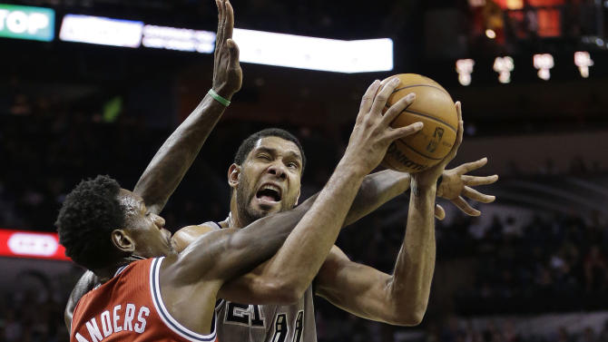 San Antonio Spurs' Tim Duncan (21) is defended by Milwaukee Bucks' Larry Sanders (8) as he tries to score during the first half of an NBA basketball game on Sunday, Jan. 19, 2014, in San Antonio