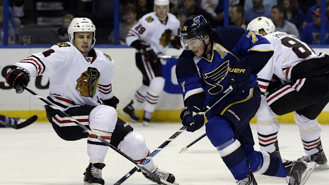 St. Louis Blues' T.J. Oshie, right, slips past Chicago Blackhawks' Niklas Hjalmarsson, of Sweden, on his way to score during the second period in Game 5 of a first-round NHL hockey playoff series Friday, April 25, 2014, in St. Louis