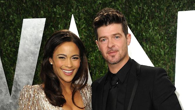 "FILE - In this Feb. 24, 2013 file photo, Paula Patton and Robin Thicke arrive at the 2013 Vanity Fair Oscars Viewing and After Party at the Sunset Plaza Hotel in West Hollywood, Calif. Thicke originally didn't plan to release the unrated version of his music video for the song ""Blurred Lines,"" which features nude models prowling around him and rappers Pharrell and T.I. Thicke said his wife was OK with the models on the set and he sought her approval: ""Obviously if she didn't like it I wouldn't put it out."" (Photo by Jordan Strauss/Invision/AP, File)"