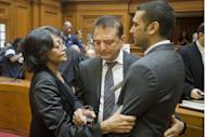 Vinod Hindocha (centre) father of murdered honeymooner Anni Dewani and his son Anish (R) are comforted by a police officer in the High Court in Cape Town. A man convicted of murdering Anni Dewani in South Africa two years ago has been sentenced to life in prison