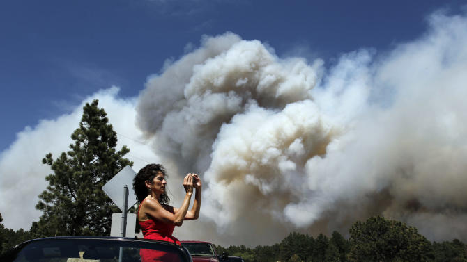 Colorado Springs resident Yolette Baca takes a photo of the wildfire in the Black Forest area north of Colorado Springs, Colo., on Wednesday, June 12, 2013. The number of houses destroyed by the Black Forest fire could grow to around 100, and authorities fear it's possible that some people who stayed behind might have died. (AP Photo/Brennan Linsley)
