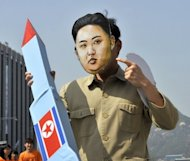 A South Korean activist wearing a mask of North Korean leader Kim Jong-Un holds a mock missile during a rally denouncing North Korea's rocket launch in April. Washington and Seoul have urged Pyongyang to scrap the latest launch while Tokyo has postponed talks originally planned this week with North Korea.