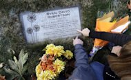 "In this Nov. 17, 2014 photo, Linda and Rob Robertson point out a quote on the headstone of the grave of their son, Ryan, in Issaquah, Wash. The couple, evangelical Christians, brought their son to ""reparative therapy"" when he came out to them as gay. His sexual orientation didn't change, and he became addicted to drugs and eventually died of an overdose. The Robertsons are now dedicated to helping other evangelical parents accept their gay children. (AP Photo/Elaine Thompson)"