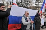 Pro-Russian activists hold a Russian flag during a rally in Simferopol on March 6, 2014