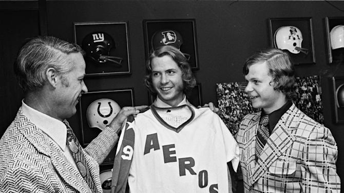 "FILE - In this June 5, 1973, file photo, Gordie Howe, left, the former NHL great, checks out the new look for his sons, Marty, center, and Mark, right, after they signed to play with the World Hockey Association team in Houston, Texas. Gordie eventually joined the team, and a made-for-TV movie, ""Mr. Hockey: The Gordie Howe Story,"" focuses on the season the Hall of Famer teamed up with his sons in Houston. The U.S. premiere of the film is Saturday, May 4, 2013. ((AP Photo/Ed Kolenovsky, File)"