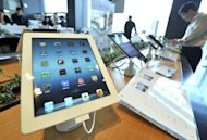 Apple's iPad is displayed at a branch of KT, a Korean distributor of iPhones and iPads in April 2012. Demand for tablet computers is growing faster than earlier forecasts, driven by strong demand for the iPad from Apple, according to a survey
