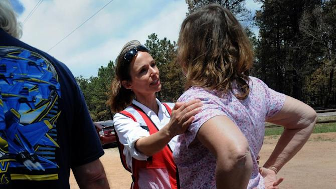 American Red Cross volunteer Denise Brill helps a resident who lost her home Tuesday, June 18, 2013, at the re-entry at the School in the Woods in Colorado Springs, Colo., as some residents were allowed to return to their homes. The Black Forest fire has destroyed 502 homes and charred more than 22 square miles. It was 85 percent contained Tuesday. (AP Photo/The Colorado Springs Gazette, Christian Murdock) MAGS OUT