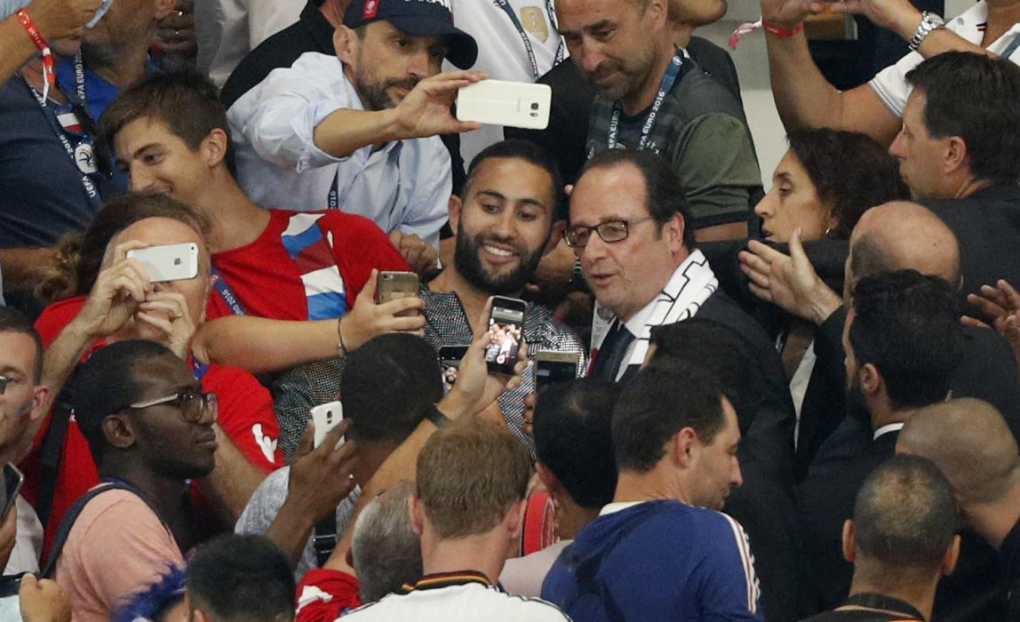 France President Francois Hollande poses for a photo in the crowd at the end of the match