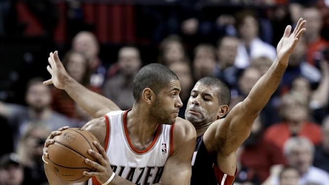 Miami Heat forward Shane Battier, right, plays tight defense against Portland Trail Blazers forward Nicolas Batum, from France, during the first half of an NBA basketball game in Portland, Ore., Saturday, Dec. 28, 2013