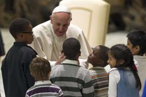 Pope Francis greets children assisted by volunteers of Santa Marta institute during an audience in the Vatican