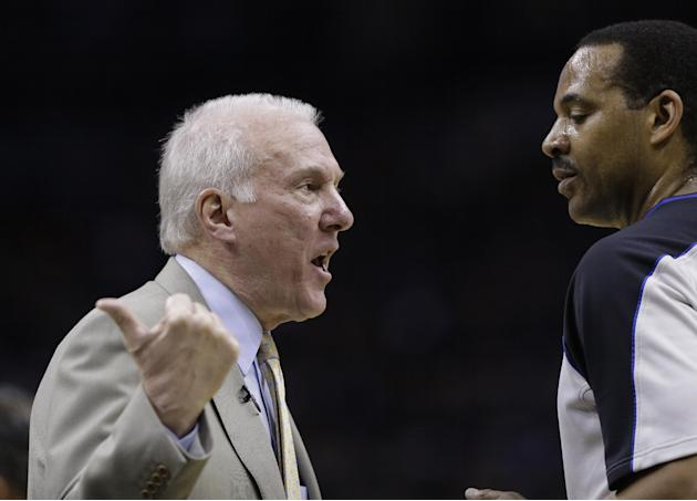 San Antonio Spurs coach Gregg Popovich, left, argues a call during the first quarter of Game 1 of the opening-round NBA basketball playoff series against the Dallas Mavericks, Sunday, April 20, 2014,