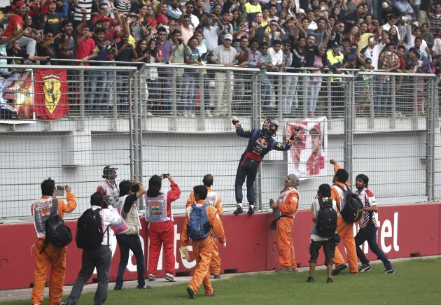 Red Bull Formula One driver Vettel throws his gloves into the crowd after winning the Indian F1 Grand Prix at the Buddh International Circuit in Greater Noida
