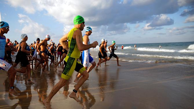 Participants run into the Mediterranean Sea as they begin the swimming section of a triathlon in Ashdod, Israel