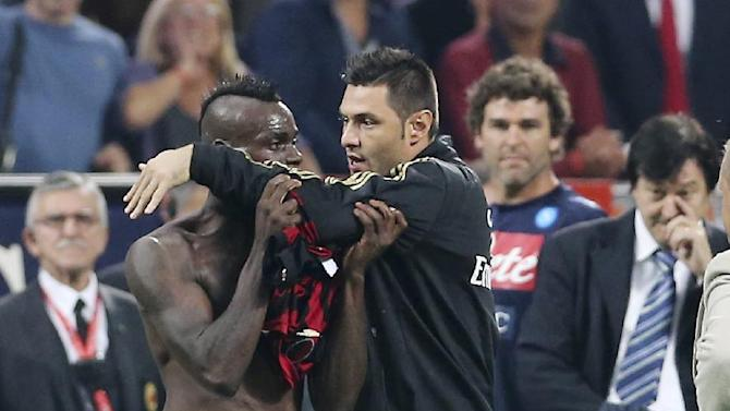 AC Milan forward Mario Balotelli, left, is restrained by teammate Marco Amelia after receiving a red card at the end of the Serie A soccer match between AC Milan and Napoli at the San Siro stadium in Milan, Italy, Sunday, Sept. 22, 2013. Napoli came away from the San Siro with a 2-1 victory over AC Milan with goals from Miguel Britos and Gonzalo Higuain, while Mario Balotelli failed to convert a penalty kick for the first time in his career