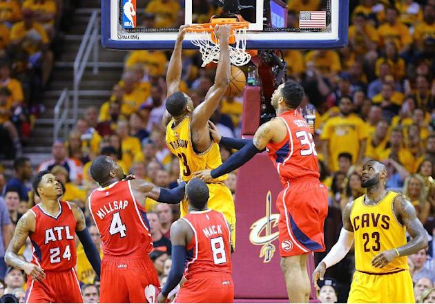 Cleveland Cavaliers' Tristan Thompson gets past Atlanta Hawks defenders Kent Bazemore, Paul Millsap, Shelvin Mack and Mike Scott, from left, for a dunk, with LeBron James watching during Game 4 of