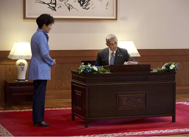 U.S. President Barack Obama sings a guest book as South Korean President Park Geun-hye looks on at the Blue House, Friday, April 25, 2014, in Seoul, South Korea. Obama is sitting down with Park, whose
