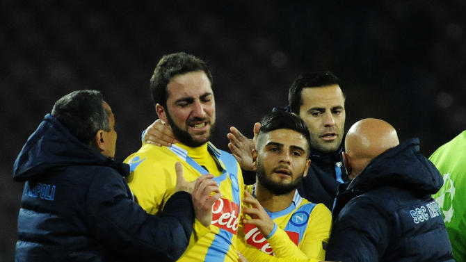 Napoli's Gonazalo Higuain, second left, is comforted by teammate Lorenzo Insigne at the end of a Champions League, group F, soccer match between Napoli and Arsenal, at the Naples San Paolo stadium, Italy, Wednesday, Dec. 11, 2013. Ten-man Arsenal advanced to the Champions League knockout phase for the 14th consecutive year despite a 2-0 loss Wednesday at Napoli, which was eliminated. Gonzalo Higuain scored in the 73rd minute but the San Paolo stadium was soon silenced when word arrived that Borussia Dortmund had scored a late goal in a 2-1 win at Marseille to win Group F