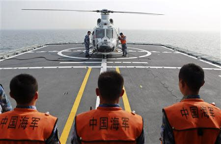 Chinese naval sailors look on as a helicopter gets ready to take off from Chinese naval frigate Linyi during multi-country maritime joint exercises off the coast in Qingdao