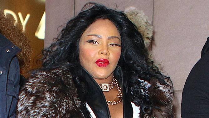 Lil Kim wears a big fur coat and fake eyelashes while out in NYC