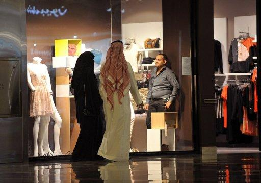 A Saudi man and woman walk past a clothes shop at a local mall in Riyadh on August 18, 2012. Saudi authorities have ordered shops employing both men and women to build separation walls to enforce the strict segregation laws of the ultra-conservative kingdom, local press reported Monday