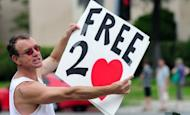 """A protester holds a placard for passing traffic on Sunset Boulevard in Hollywood in front of a Chick-fil-A fast food restaurant. Gays and lesbians puckered up at """"kiss-ins"""" outside Chick-fil-A outlets across the United States in protest over the fast-food chain's opposition to same-sex marriage"""