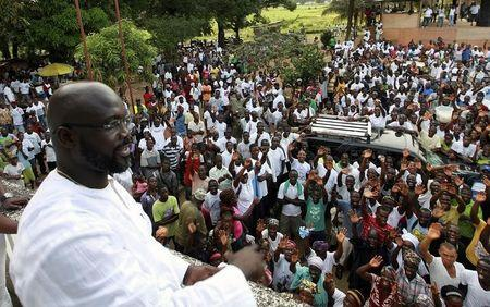 George Weah, a former soccer star and the running mate of presidential candidate Winston Tubman of the Congress for Democratic Change (CDC), looks on as he stands at the balcony after a news conference at his headquarters in Monrovia November 5, 2011. REUTERS/Luc Gnago/Files
