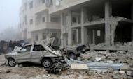A handout picture released by the Syrian Arab News Agency (SANA) shows Syrians inspecting the site of a suicide car bombing in Salmiyeh, a town in the central province of Hama, on January 22, 2013.
