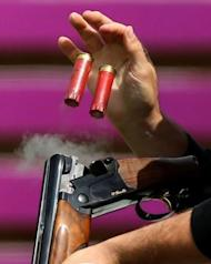 World and Olympic record holder Vincent Hancock of the United States catches empty cartridges as he competes in the men's skeet qualification at The Royal Artillery Barracks in London on July 30, 2012, for The London 2012 Olympic Games